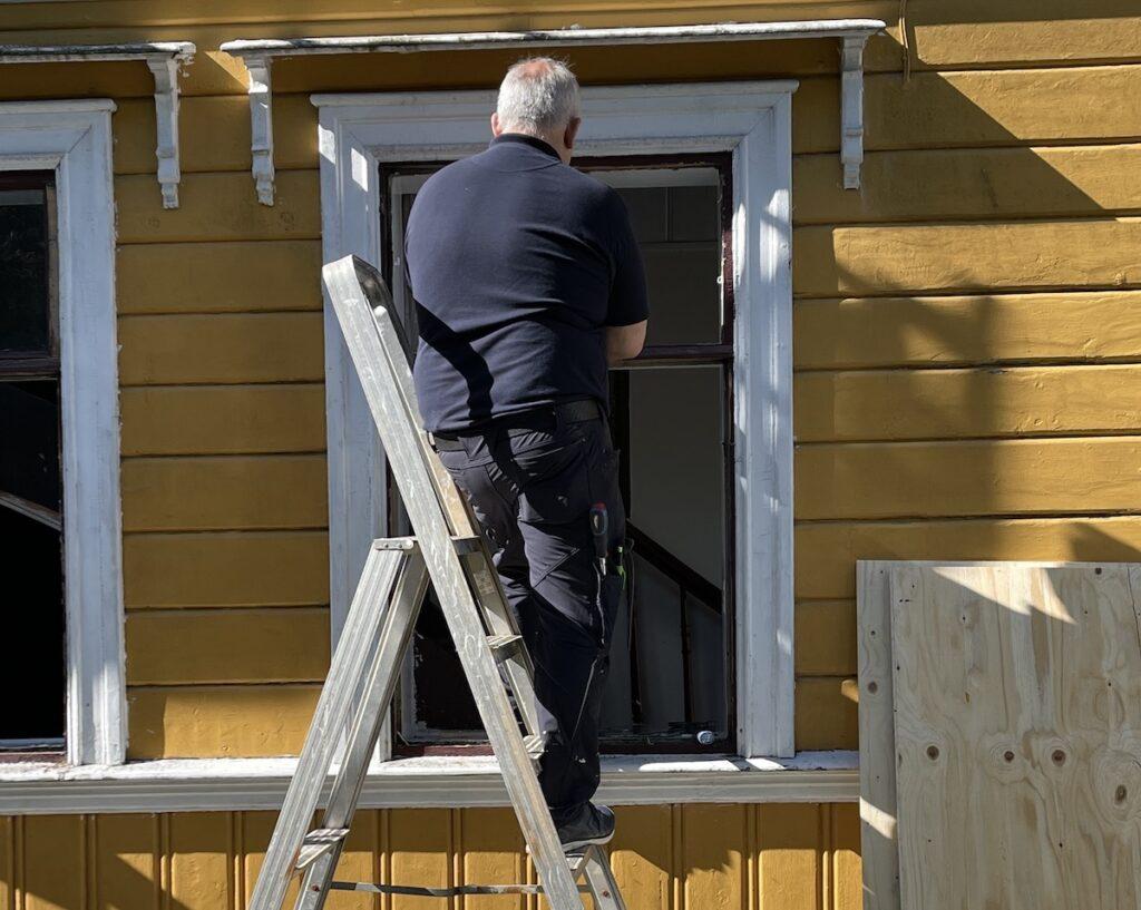 Fjellsiden - bilde av mann fra Bergen Håndtverksenter som fjerner vinduer